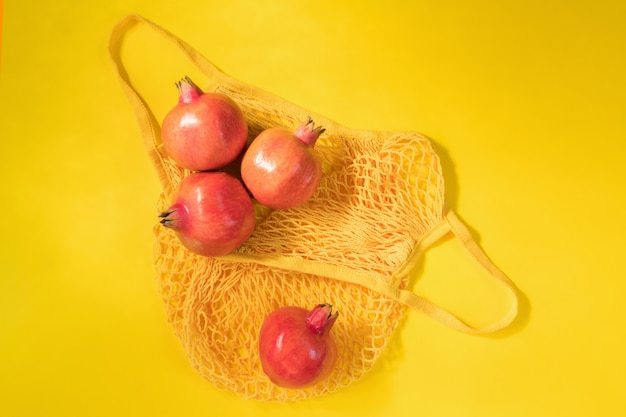 Romã madura fresca em rede de algodão ecológico ou sacola de compras de malha