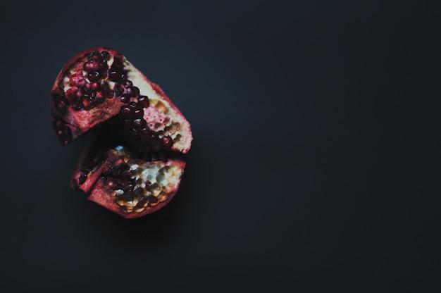 Romã vermelha do frescor maduro com semente, grões no fundo escuro.
