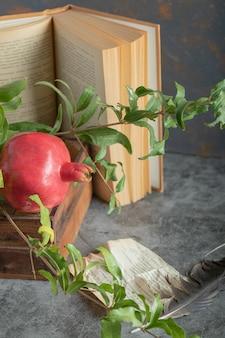 Romã vermelha em caixa de madeira com livro e folhas