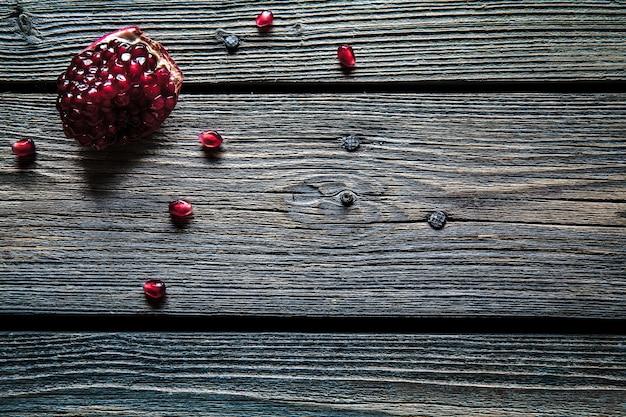 Romã vermelha fresca e toranja em um fundo de madeira. romã em placa com fundo de madeira. romã em plano de fundo texturizado de madeira. imagem de visão aérea.