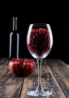 Romã vinho romã no copo de vinho na mesa de madeira
