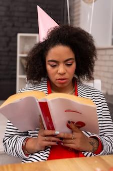 Romance de amor. agradável mulher afro-americana segurando um livro enquanto o lê