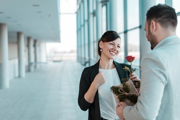 Romance de escritório. homem que dá uma rosa ao seu colega de trabalho do sexo feminino.