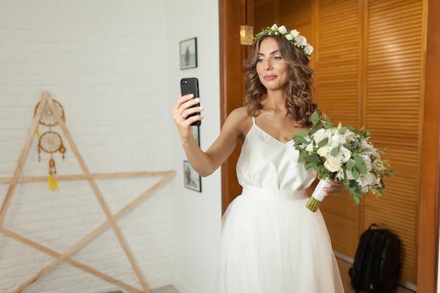 Romântica e feliz noiva caucasiana em elegante vestido de noiva tomando selfie