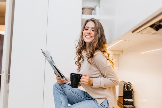 Romântica garota de cabelos escuros em jeans segurando uma xícara preta e sorrindo