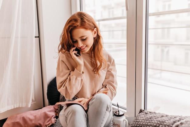 Romântica garota ruiva lendo livro ao lado da janela. jovem europeia tímida falando no telefone.