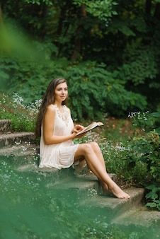 Romântica jovem de cabelos compridos com os pés descalços, senta-se em uma escada ao ar livre e lê um livro