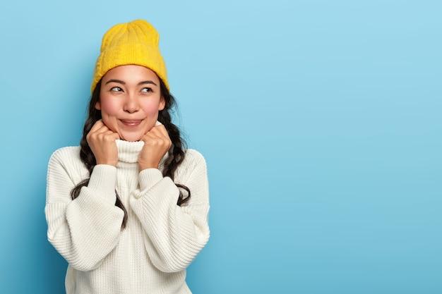 Romântica linda adolescente asiática relembra um momento agradável, usa chapéu amarelo e suéter branco quente, mantém as mãos na gola, pensando profundamente durante o dia frio de inverno
