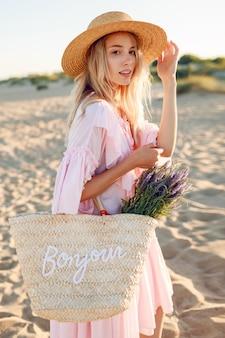 Romântica mulher branca no chapéu da moda e elegante vestido rosa posando na praia. segurando o saco de palha e buquê de flores.