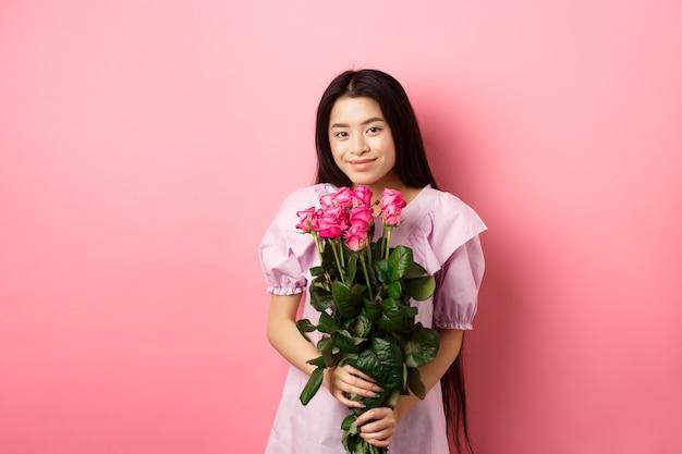 Romântica terna menina asiática segurando buquê de rosas, sorrindo fofo para a câmera, tendo o encontro dos namorados com o amante, usando vestido, fundo rosa.