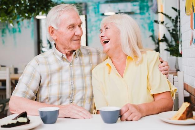 Romântico casal maduro feliz sentado no café e abraçando