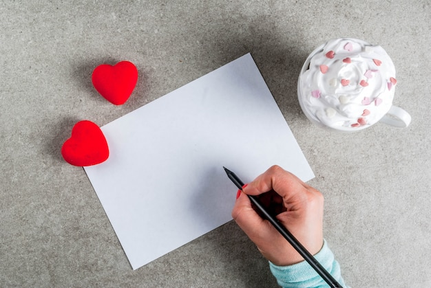Romântico, dia dos namorados. menina escrevendo a mão na foto no papel em branco para carta, parabéns, chocolate quente com chantilly e corações doces, vista superior