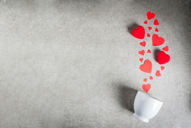 Romântico, dia dos namorados. uma mesa de pedra cinza com uma xícara de café ou chocolate quente, decorada com papel e corações vermelhos de pelúcia, vista superior plana