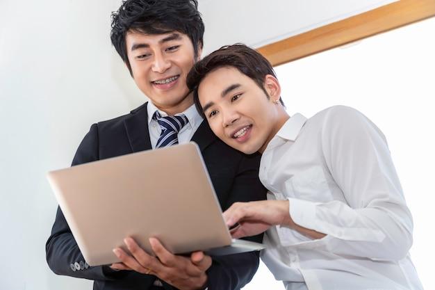 Romântico e relaxar o tempo. casal homossexual asiático na suíte de compras on-line com o computador portátil juntos em casa. conceito lgbt gay.