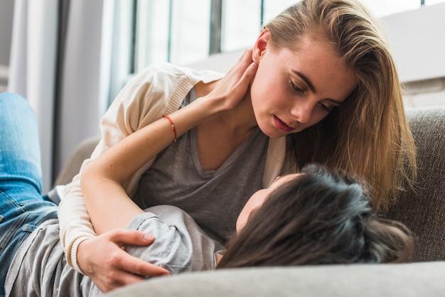Romântico jovem casal de lésbicas deitada no sofá olhando uns aos outros