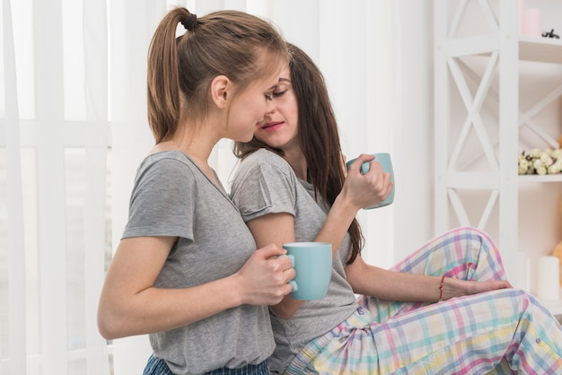 Romântico jovem casal de lésbicas segurando a xícara de café na mão