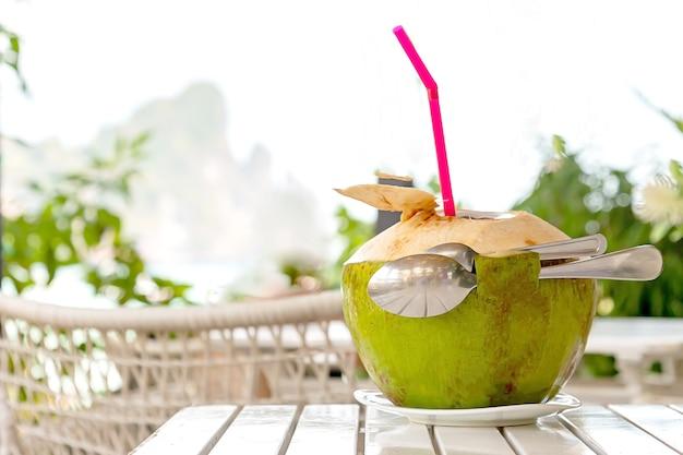 Romântico para dois suco de coco fresco com canudo e duas colheres na mesa de madeira branca praia borrada