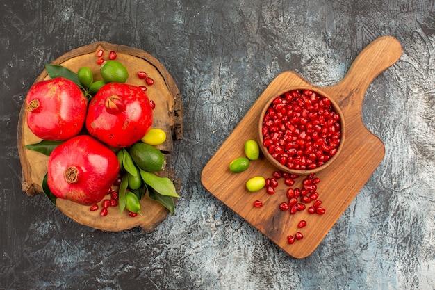 Romãs de romã e tigela de sementes de romã nas tábuas de corte Foto gratuita