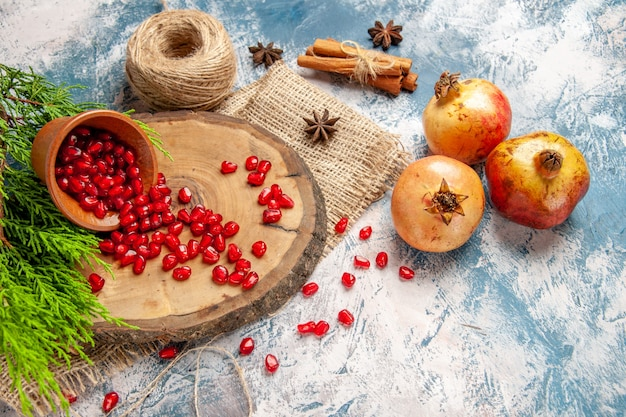 Romãs de vista frontal espalharam sementes de romã em uma tigela na placa de madeira da árvore, fio de palha, sementes de anis canela no fundo azul e branco