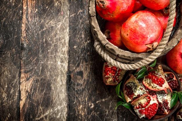 Romãs frescas em balde de madeira. sobre um fundo de madeira.