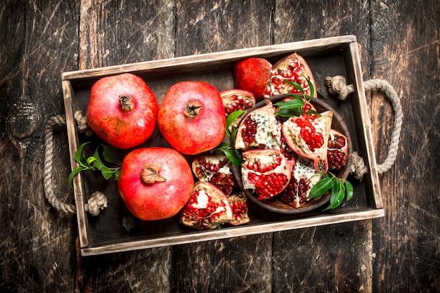 Romãs frescas em uma bandeja. sobre um fundo de madeira.