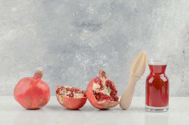Romãs frescas vermelhas e suco fresco na mesa branca.