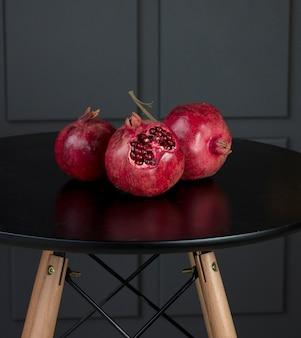 Romãs grandes sazonais vermelhas sobre uma mesa preta com suportes de madeira