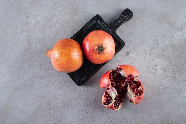 Romãs maduras frescas com sementes colocadas no quadro negro.