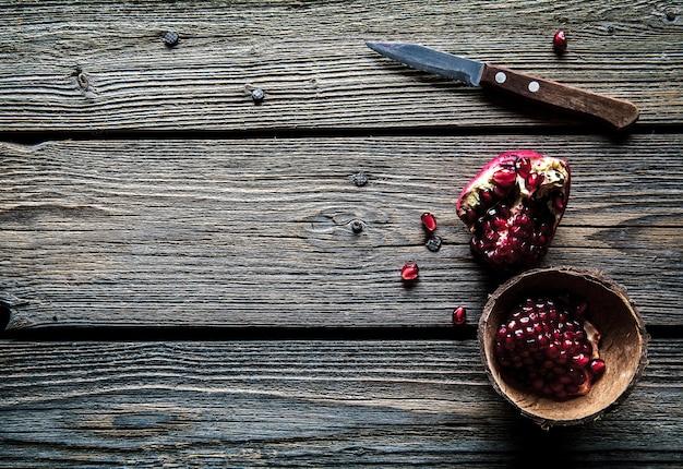 Romãs maduras, guardanapo e faca de mesa em fundo branco de madeira