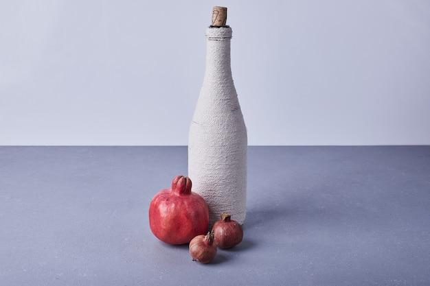 Romãs vermelhas com uma garrafa de vinho.