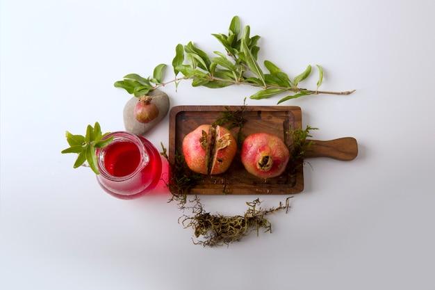 Romãs vermelhas e molho na tábua de madeira