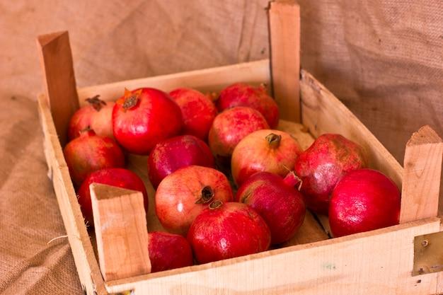 Romãs vermelhas maduras em uma caixa de madeira na serapilheira marrom