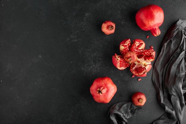 Romãs vermelhas na toalha de mesa preta e na superfície.