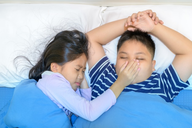 Ronco irritante. a irmã cobriu a boca do irmão.