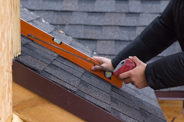Roofer segurando uma fita métrica e nível de bolha em suas mãos sobre as telhas recém-instaladas em uma nova construção de casa de madeira