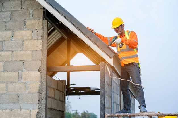 Roofer, trabalhando na estrutura do telhado do edifício no canteiro de obras, trabalhador que instala o telhado do metal no telhado da casa nova.