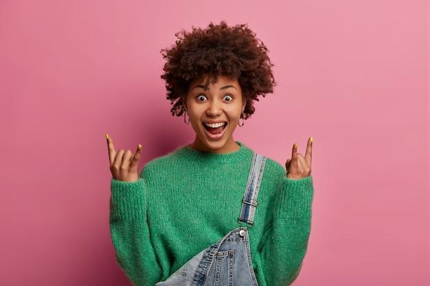 Roqueira rebelde e bonita com penteado afro curtindo uma música legal no show