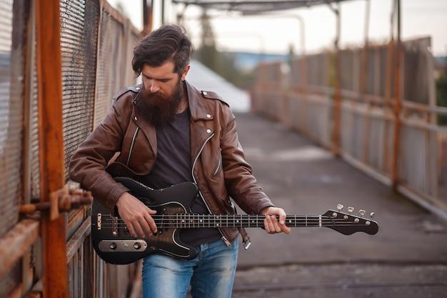 Roqueiro barbudo com cabelos grisalhos em uma jaqueta de couro marrom e jeans azul se levanta e segura uma guitarra elétrica preta contra o fundo de uma estrada