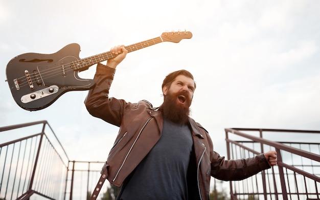 Roqueiro barbudo e brutal, de cabelo grisalho, com jaqueta de couro marrom e jeans azul, segura uma guitarra elétrica na mão e grita