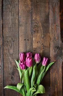 Rosa, bando de tulipas no fundo de pranchas de madeira do celeiro escuro