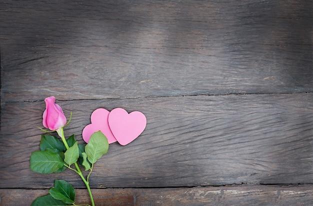 Rosa com alguns corações em um fundo de madeira. flor rosa com corações rosa com espaço de cópia em fundo escuro de madeira