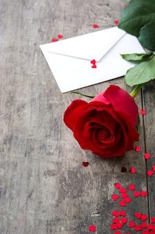 Rosa com envelope e corações em fundo de madeira