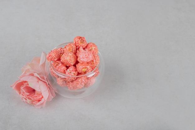 Rosa corola e uma tigela de vidro de pipoca na mesa de mármore.