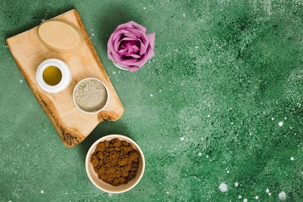 Rosa de ervas oval; óleo; barro de rhassoul; pó de café e rosa roxa no plano de fundo texturizado verde
