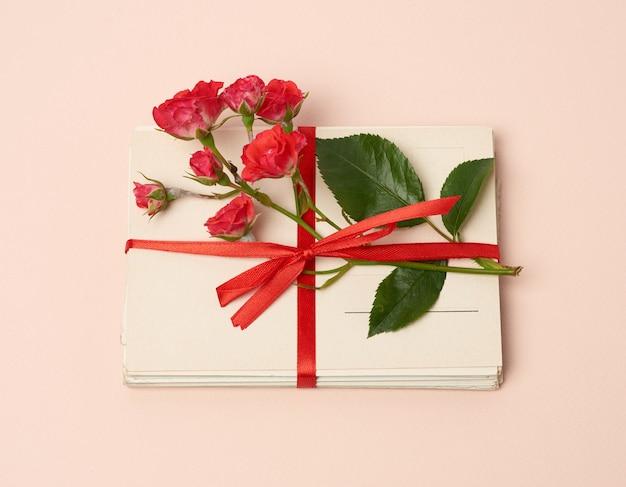 Rosa de florescência vermelha, pilha de cartões de papel vintage em um fundo bege