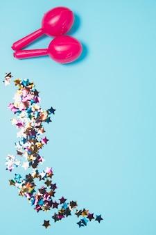 Rosa dois maracas com confetes coloridos da forma da estrela contra o fundo azul