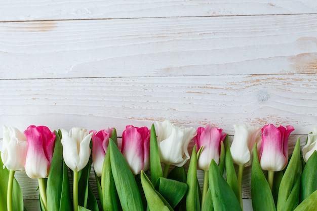 Rosa e tulipas brancas na superfície de madeira branca