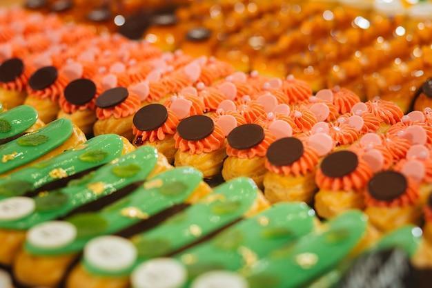 Rosa e verde. éclairs rosa com pedaços de chocolate na parte superior e eclairs verdes com sabor de menta sendo colocados juntos