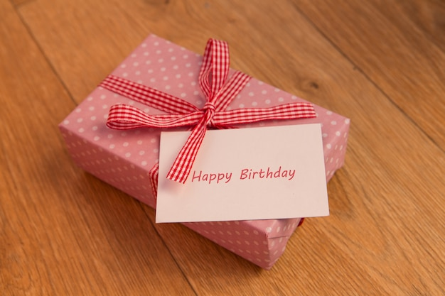 Rosa embrulhado presente com saudação de cartão de aniversário