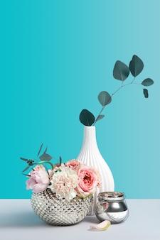 Rosa floresce em um vaso elegante de metal na mesa cinza contra o fundo de cor. conceito de loja de flores com itens de decoração. minimalismo ainda vida composição com espaço para o projeto.
